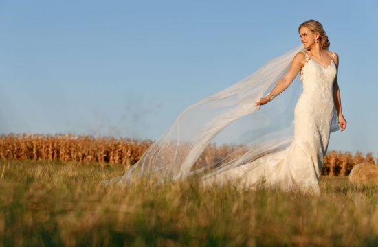 Bride walking through the grass fields at Lezar Opstal in Heidelberg