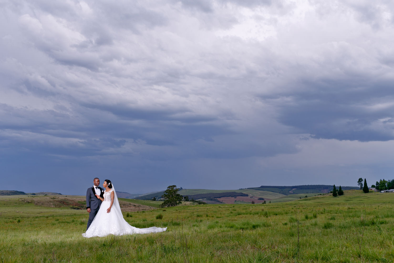 African wedding couple standing on a green hill at Brahman Hills Nottingham Road Natal Midlands