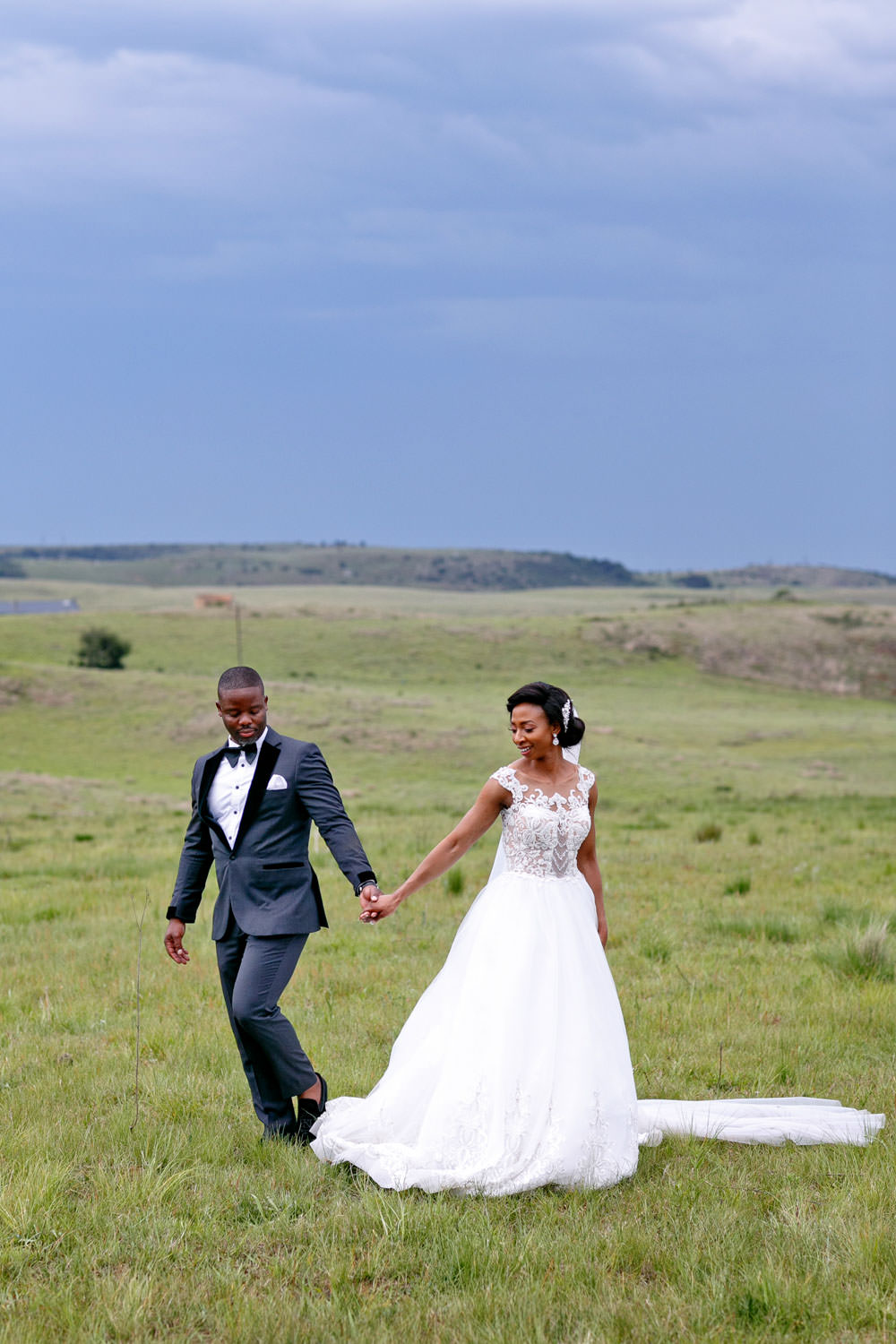 Bride and groom walking in the green grass fields at a wedding venue in Natel